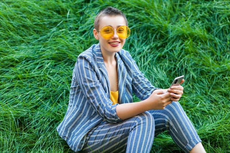 俏丽的年轻短发妇女画象偶然蓝色镶边衣服的,黄色玻璃坐拿着她的智能手机的草 免版税库存图片