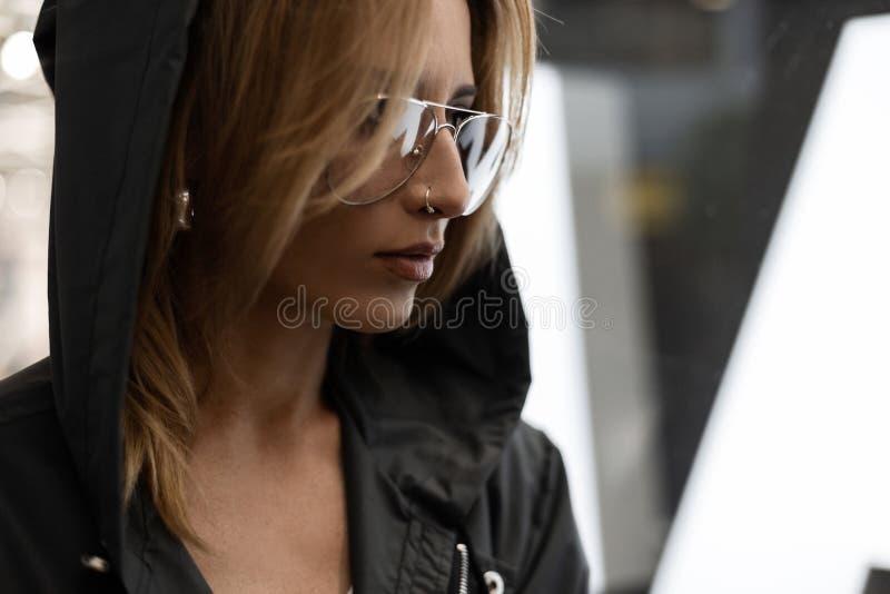 俏丽的年轻美丽的红发妇女的面孔画象与性感的嘴唇的有刺穿的在葡萄酒玻璃的一件戴头巾夹克 免版税库存照片