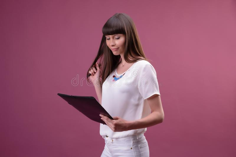 俏丽的年轻美女身分,文字,作为笔记,在手中拿着课本组织者和笔 免版税库存照片