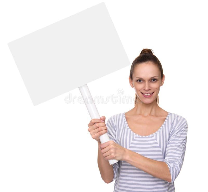 俏丽的微笑的女孩举行在棍子的一张招贴 免版税图库摄影