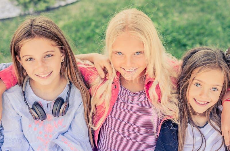 俏丽的微笑的女孩顶视图坐一起拥抱 免版税库存照片