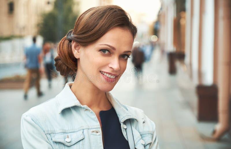 俏丽的微笑的妇女在城市 户外纵向 库存图片