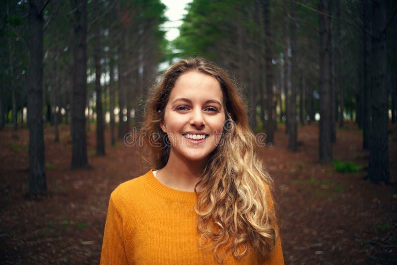 俏丽的微笑的白肤金发的年轻女人在森林里 库存照片