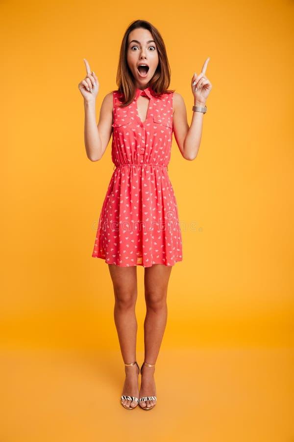 俏丽的惊奇的妇女全长画象红色礼服poin的 免版税库存图片