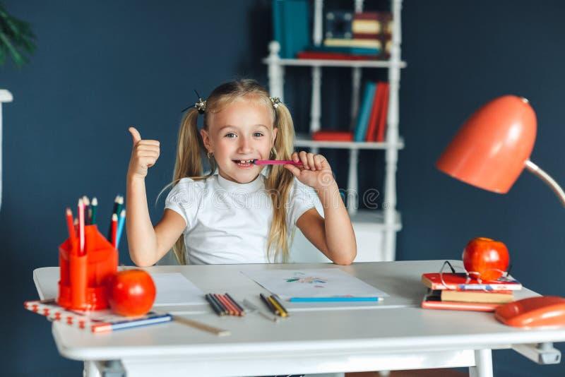 俏丽的愉快的女孩安装在她的嚼她的铅笔的书桌看照相机作白日梦与美好的微笑的天花板  库存图片