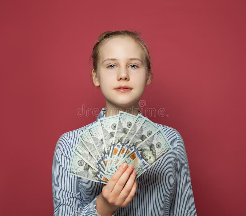 俏丽的愉快的青少年的女孩和金钱在桃红色背景的美元 库存照片