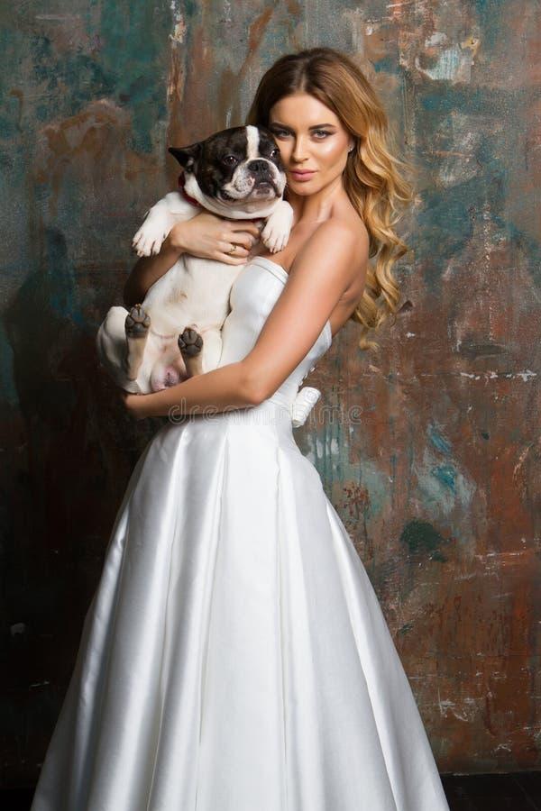 俏丽的新娘拿着一条狗 免版税库存照片