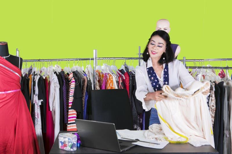 俏丽的时尚编辑拿着在演播室的一种织品 免版税图库摄影