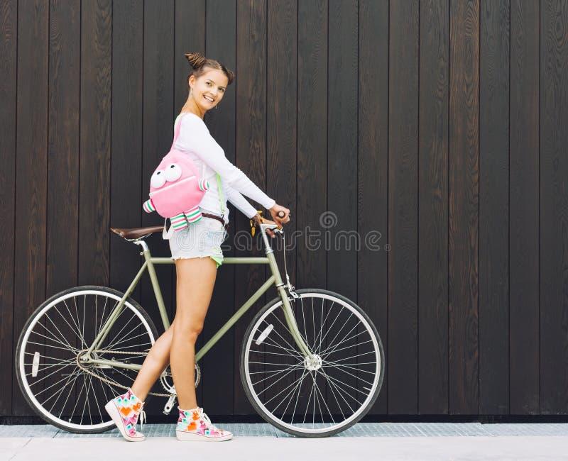 俏丽的有一个滑稽的桃红色背包立场的女孩简而言之和T恤杉与他的自行车固定在齿轮nex木板条太阳墙壁  免版税库存照片