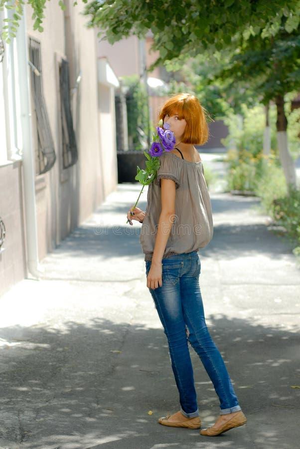 俏丽的有紫色玫瑰的红头发人十几岁的女孩由绿色离开bac 免版税库存图片