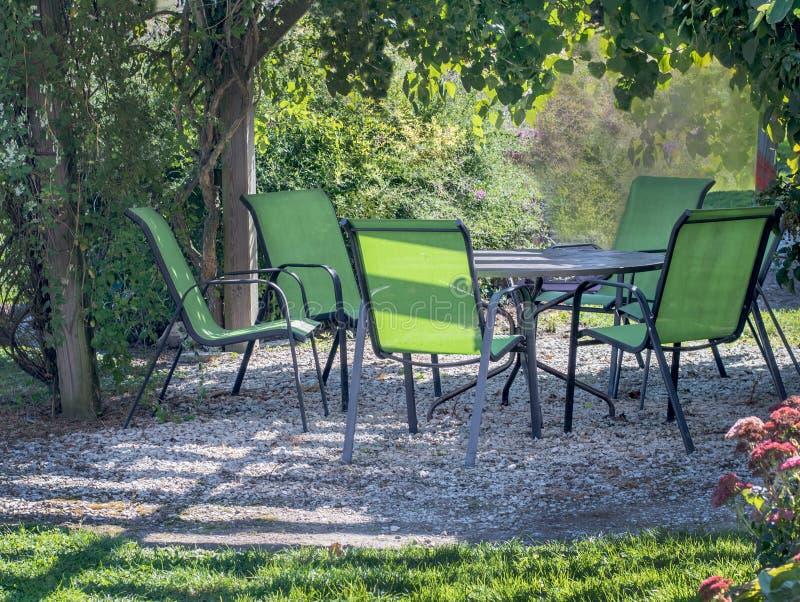 俏丽的桌和椅子在一个绿色庭院树荫处下 库存图片