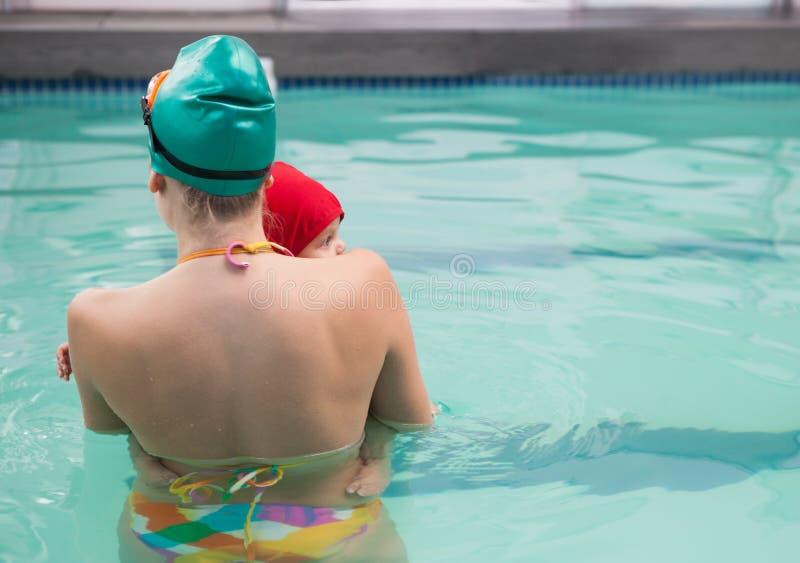 俏丽的母亲和婴孩游泳池的 免版税库存图片