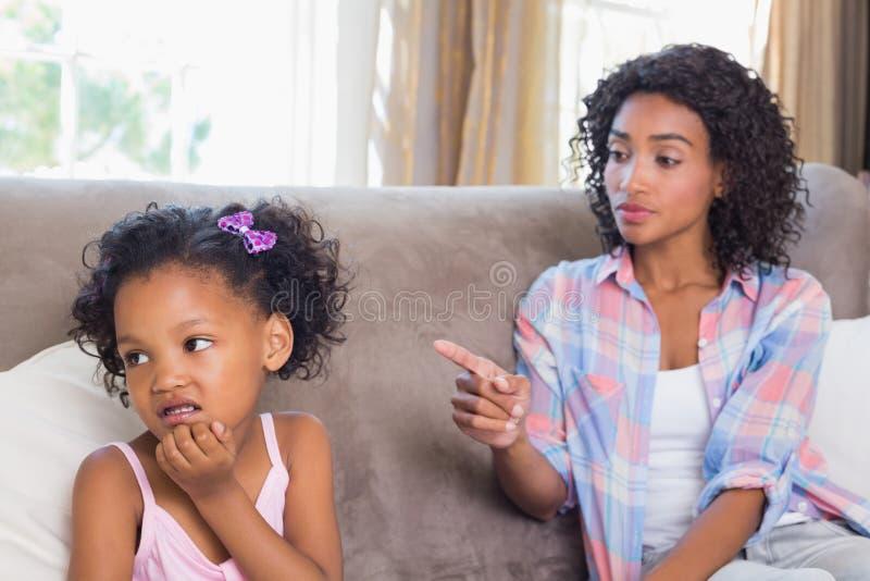 俏丽的母亲坐责骂易怒的女儿的长沙发 库存图片