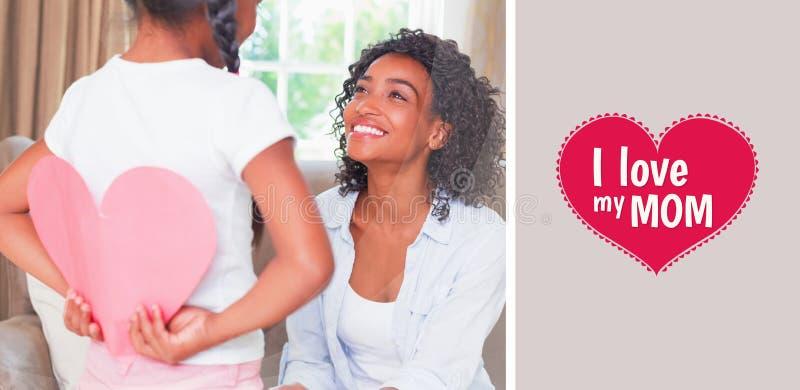 俏丽的母亲的综合图象坐有女儿掩藏的心脏卡片的长沙发 免版税库存照片