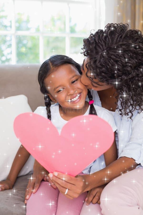 俏丽的母亲的综合图象坐有女儿读书心脏卡片的长沙发 免版税库存照片