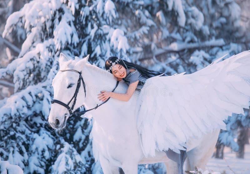 俏丽的深色头发的夫人在一匹白色大马,一件长的灰色雨衣的一个女孩说谎有在她的头的一件银色装饰品的 免版税图库摄影