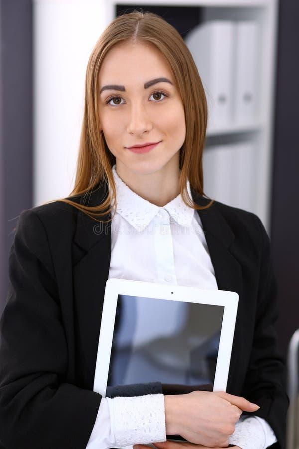 俏丽的深色的企业夫人在一件黑夹克的办公室 免版税库存照片