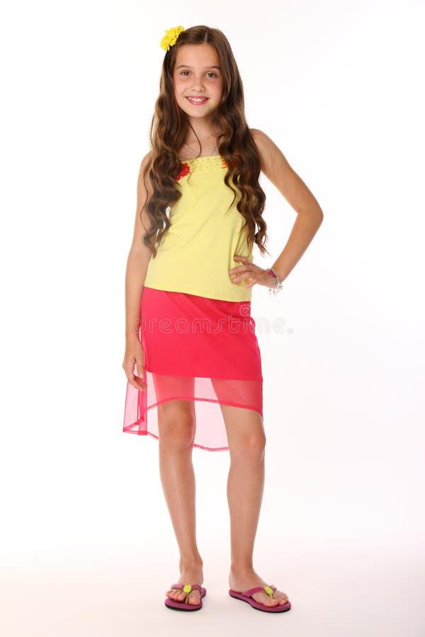 俏丽的深色的儿童女孩是在一条红色裙子的立场有光秃的腿和微笑的 免版税图库摄影