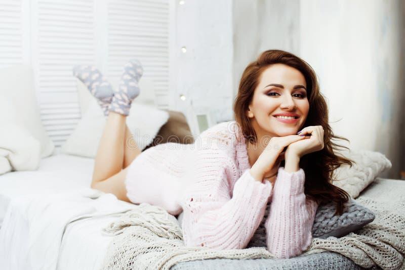 年轻俏丽的深色的女孩放置在与咖啡佩带的羊毛冬天毛线衣愉快微笑的舒适床上的,生活方式人 免版税库存照片