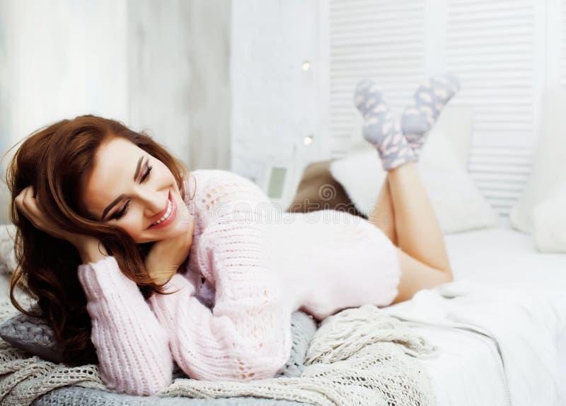 年轻俏丽的深色的妇女在她的坐在窗口,愉快的微笑的生活方式人概念的卧室 免版税库存照片