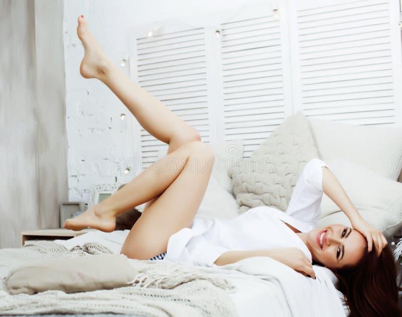 年轻俏丽的深色的妇女在她的坐在窗口,愉快的微笑的生活方式人概念的卧室 免版税库存图片