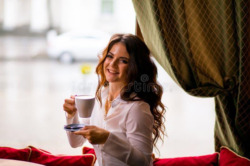 俏丽的深色的妇女用在咖啡馆和微笑的长发饮用的咖啡 库存照片