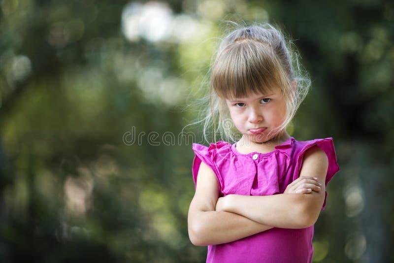俏丽的滑稽的喜怒无常的不快乐的年轻白肤金发的儿童女孩画象感到桃红色无袖的礼服的恼怒和不满意在弄脏 免版税库存照片