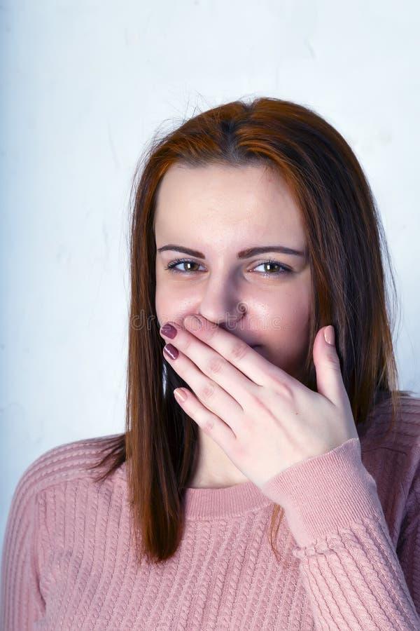 俏丽的激动的妇女幸福微笑用手盖她的嘴棕榈,年轻可爱的女孩穿桃红色毛线衣 库存图片