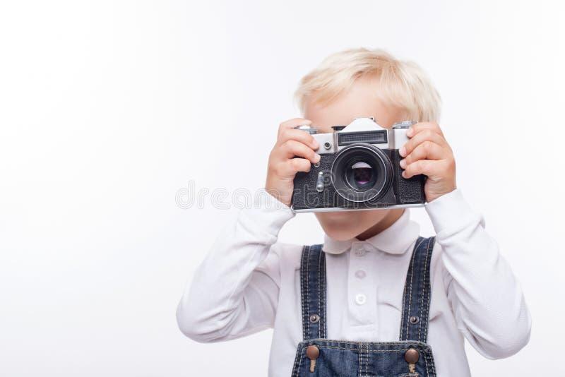 俏丽的男孩做充满喜悦的照片 免版税库存照片