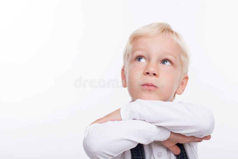 俏丽的男小学生考虑某事 免版税库存照片