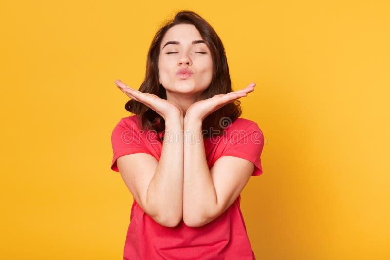 俏丽的白种人妇女接近的画象做与嘴唇的亲吻,保留两只手在下巴,佩带的偶然红色T恤杉下,摆在 免版税图库摄影