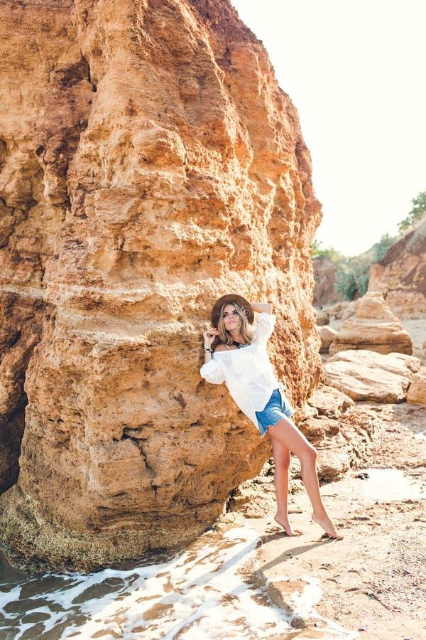 俏丽的白肤金发的女孩全lengh照片有摆在海滩的照相机的长发的在岩石背景 她佩带 库存照片