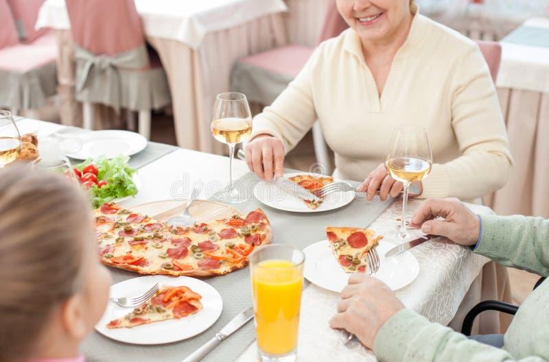 俏丽的祖父母吃与孩子的晚餐 库存照片