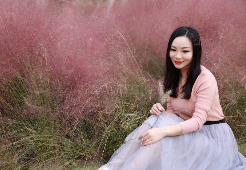 俏丽的美好的逗人喜爱的亚洲中国妇女女孩感受自由晚安祈祷花田秋天秋天公园草草坪希望自然 免版税库存图片