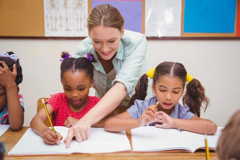 俏丽的老师帮助的学生在教室 免版税图库摄影