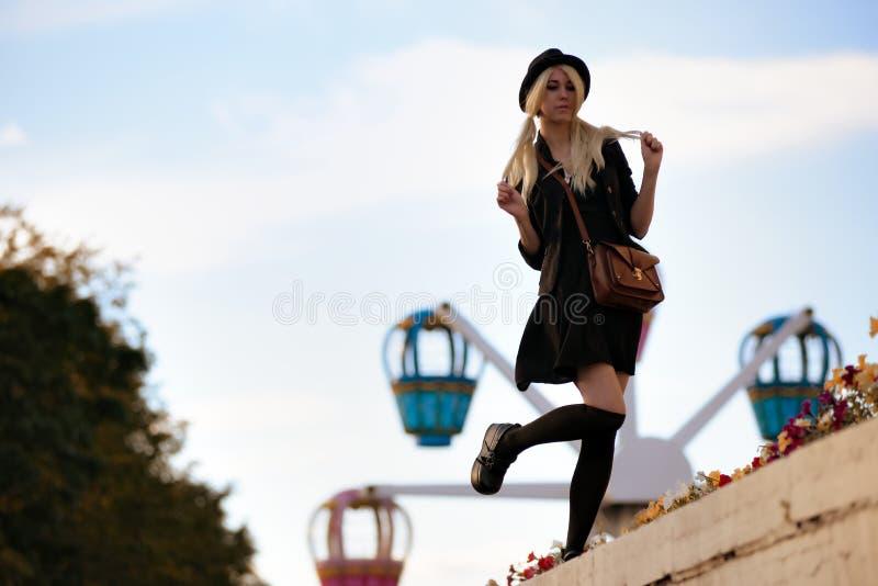 年轻俏丽的行家女孩室外在晴天,佩带的偶然衣商帽子 免版税库存照片