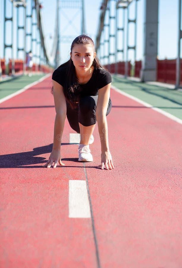 俏丽的赛跑者女孩在开始状态准备好短跑 库存图片