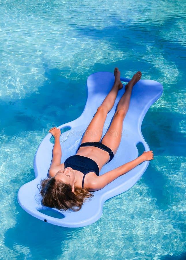 俏丽的运动在度假晒黑漂浮在一游泳场的一个水池浮游物的女孩 免版税图库摄影
