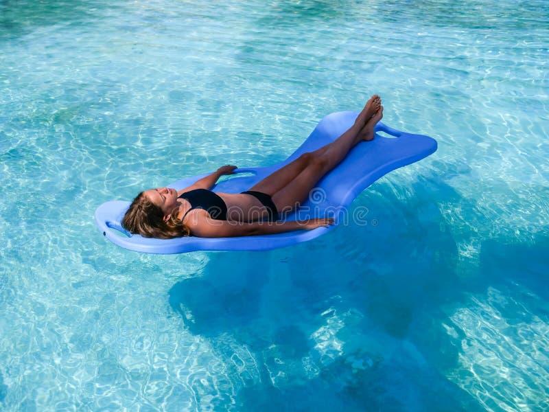 俏丽的运动在度假晒黑漂浮在一游泳场的一个水池浮游物的女孩 免版税库存图片
