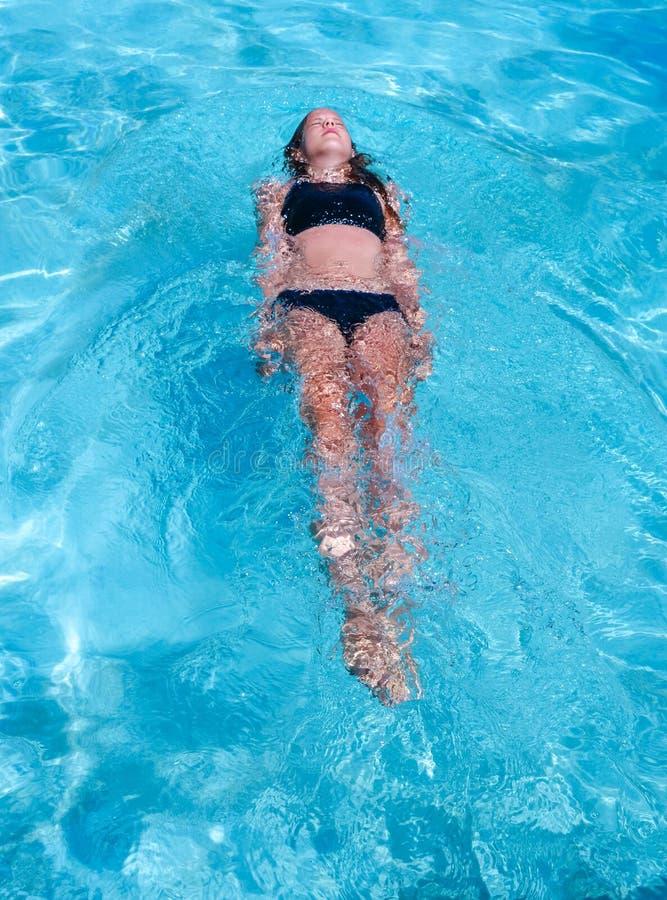 俏丽的运动在度假晒黑漂浮在一游泳场的女孩 免版税库存图片