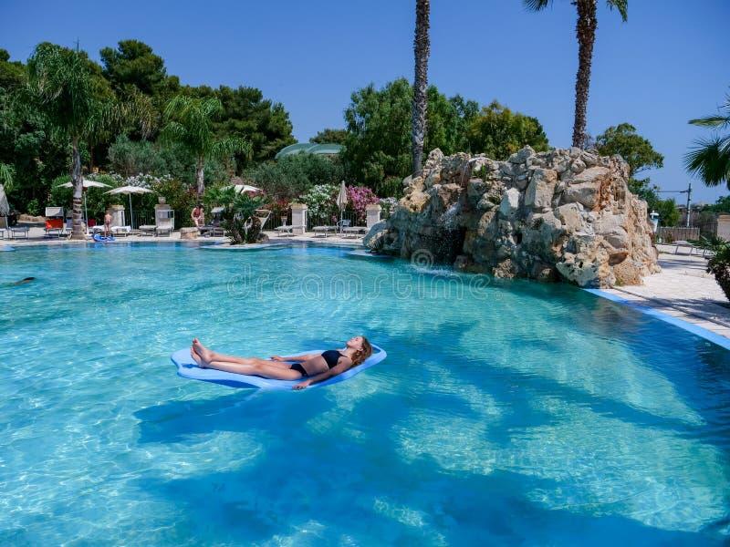 俏丽的运动在度假晒黑漂浮在一美好的游泳场的一个水池浮游物的女孩 免版税库存照片