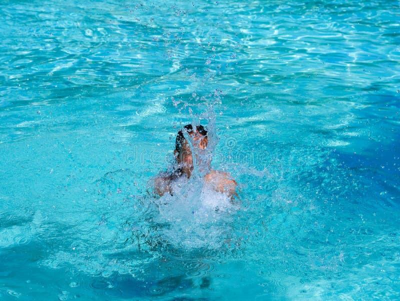 俏丽的运动晒黑飞溅在游泳场的女孩在度假 免版税库存照片