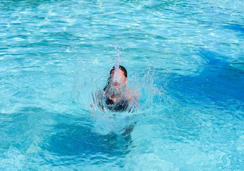 俏丽的运动晒黑飞溅在游泳场的女孩在度假 库存图片