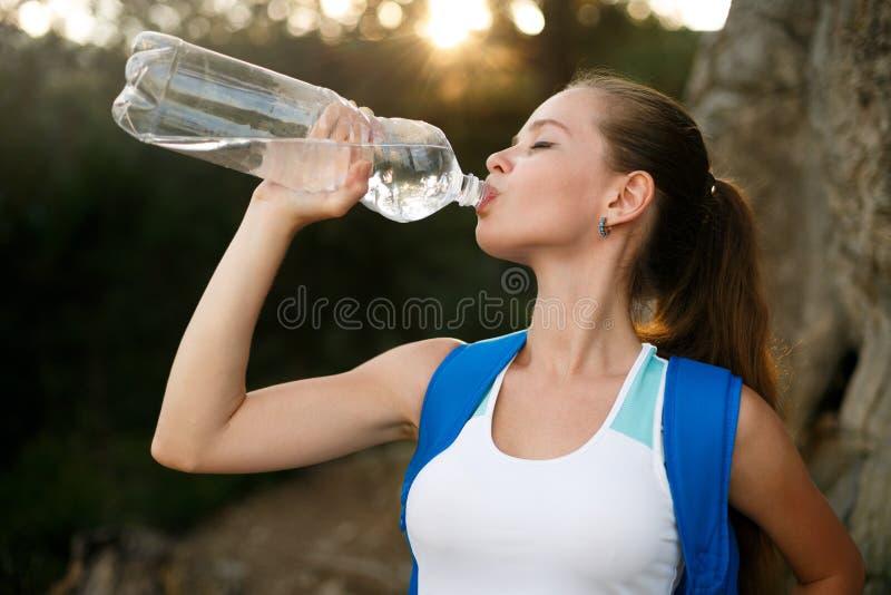 俏丽的远足者女孩饮用水 有背包饮用水的匀称妇女游人本质上 白种人女性饮料 库存图片