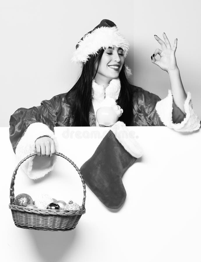 俏丽的逗人喜爱的圣诞老人女孩或微笑的妇女红色毛线衣和新年帽子的拿着装饰圣诞节或xmas桶 免版税图库摄影