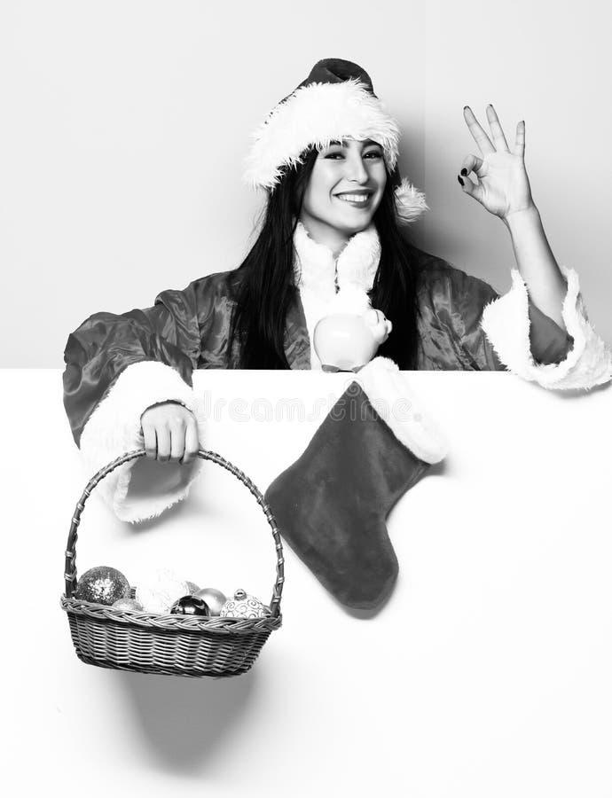 俏丽的逗人喜爱的圣诞老人女孩或微笑的妇女红色毛线衣和新年帽子的拿着装饰圣诞节或xmas桶 库存照片