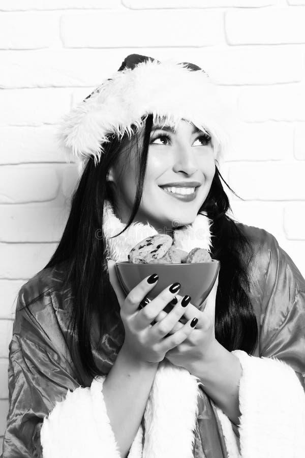 俏丽的逗人喜爱的圣诞老人女孩或微笑的愉快的深色的妇女在新年毛线衣和帽子举行圣诞节或xmas 免版税库存图片