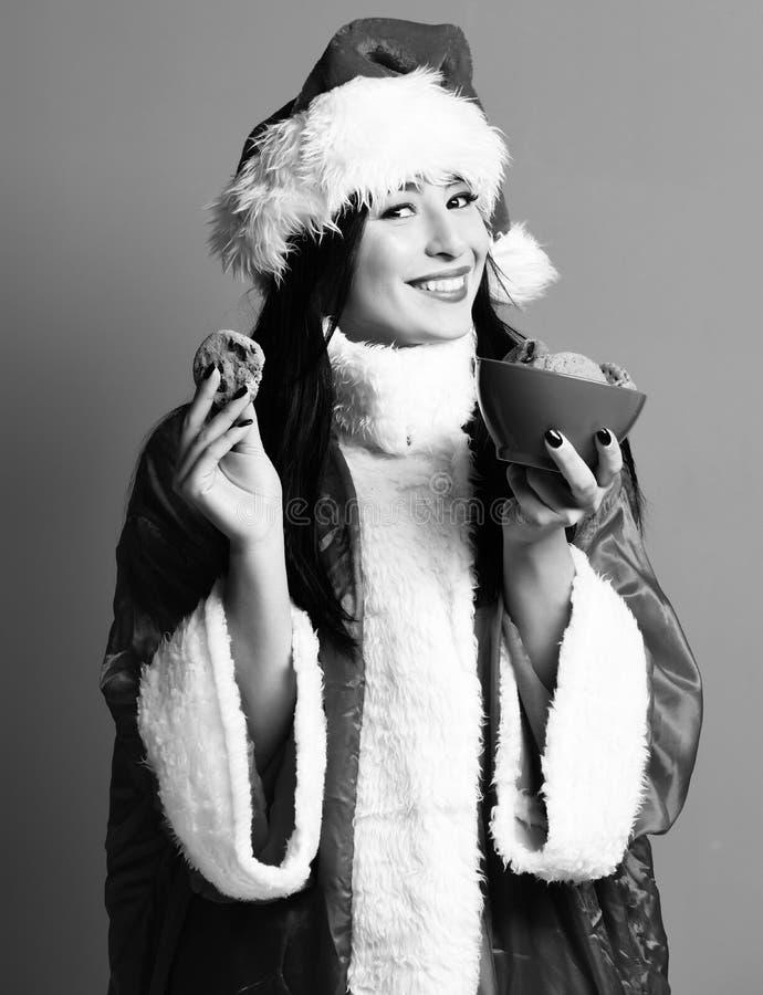 俏丽的逗人喜爱的圣诞老人女孩或微笑的深色的妇女新年毛线衣和帽子举行圣诞节或xmas巧克力臀部的 免版税库存照片