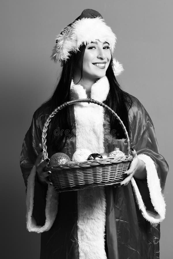 俏丽的逗人喜爱的圣诞老人女孩或微笑的深色的妇女新年毛线衣和帽子的举行装饰圣诞节或xmas 库存照片