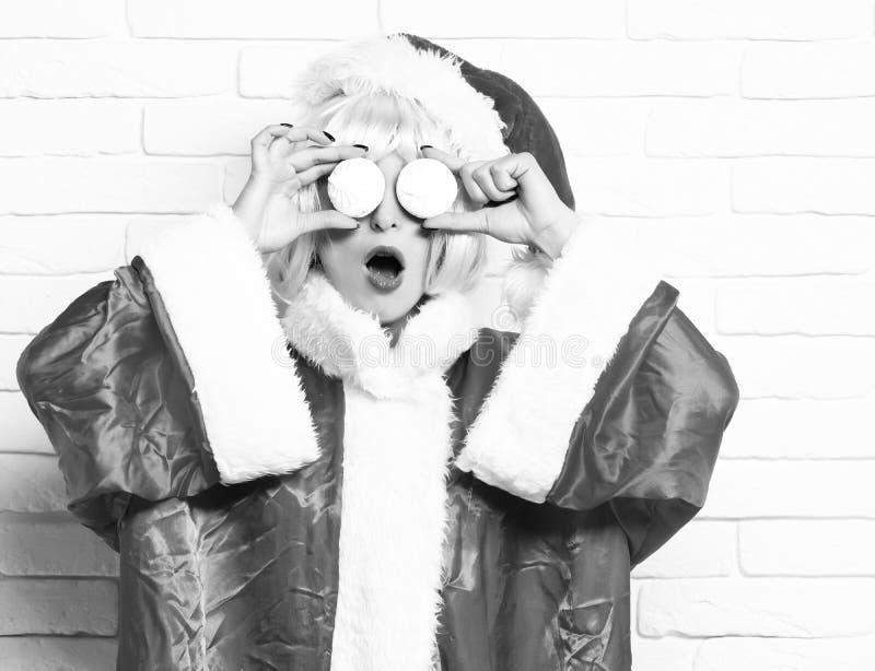 俏丽的逗人喜爱的圣诞老人女孩或惊奇的深色的妇女新年红色毛线衣和圣诞节帽子的在桃红色假发举行xmas 免版税库存照片